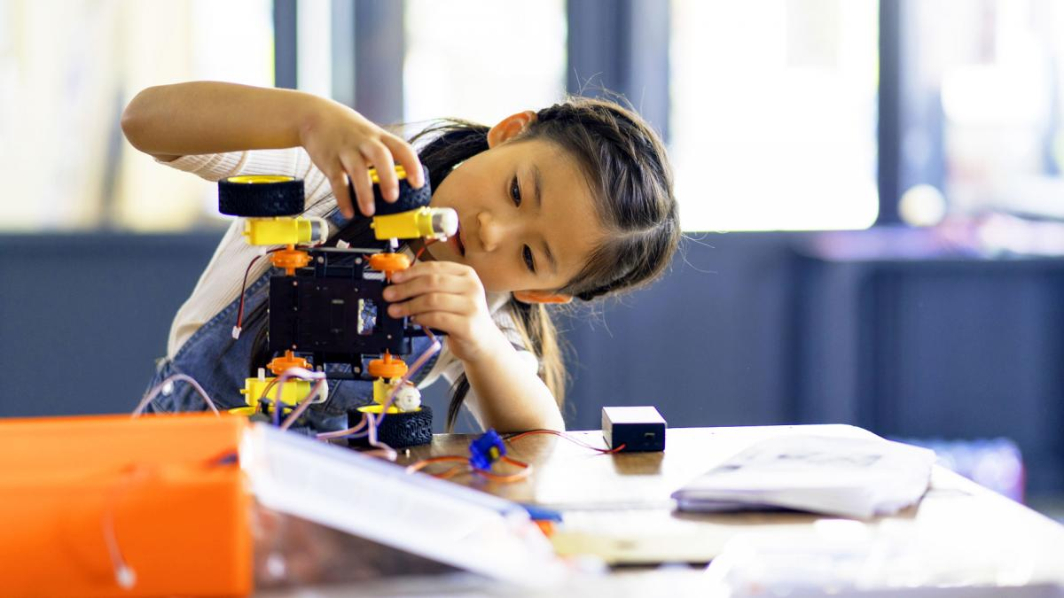 Young girl building a robot