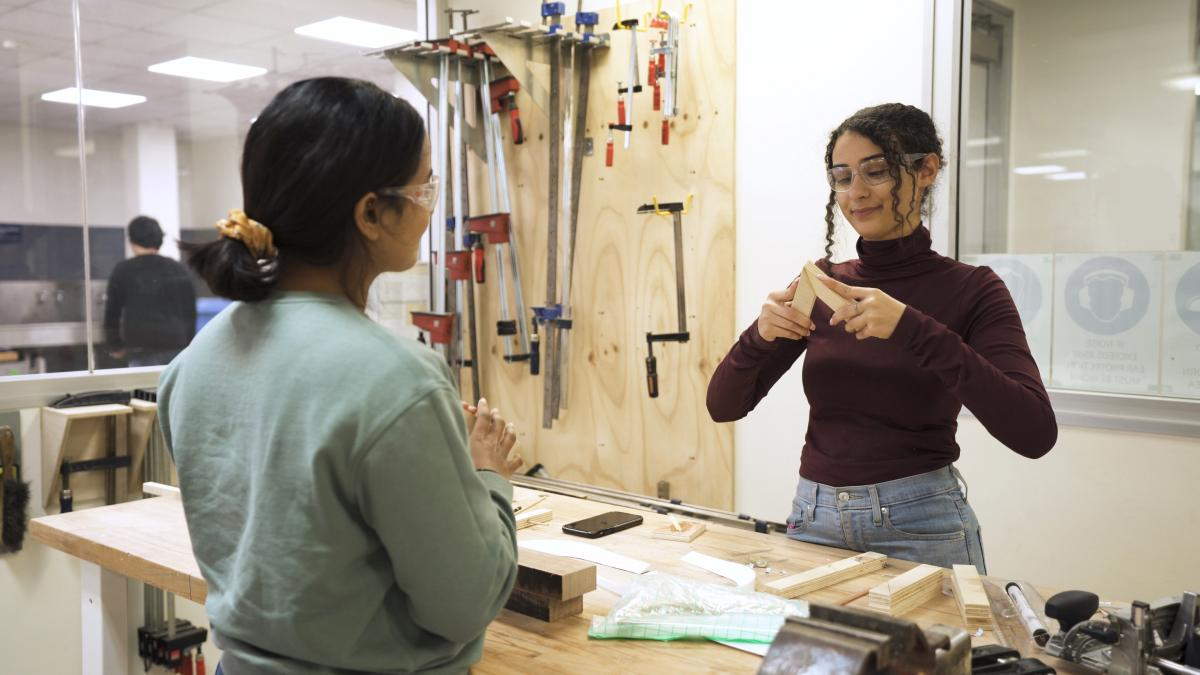 Photo of two girls making things with wood in a workshop