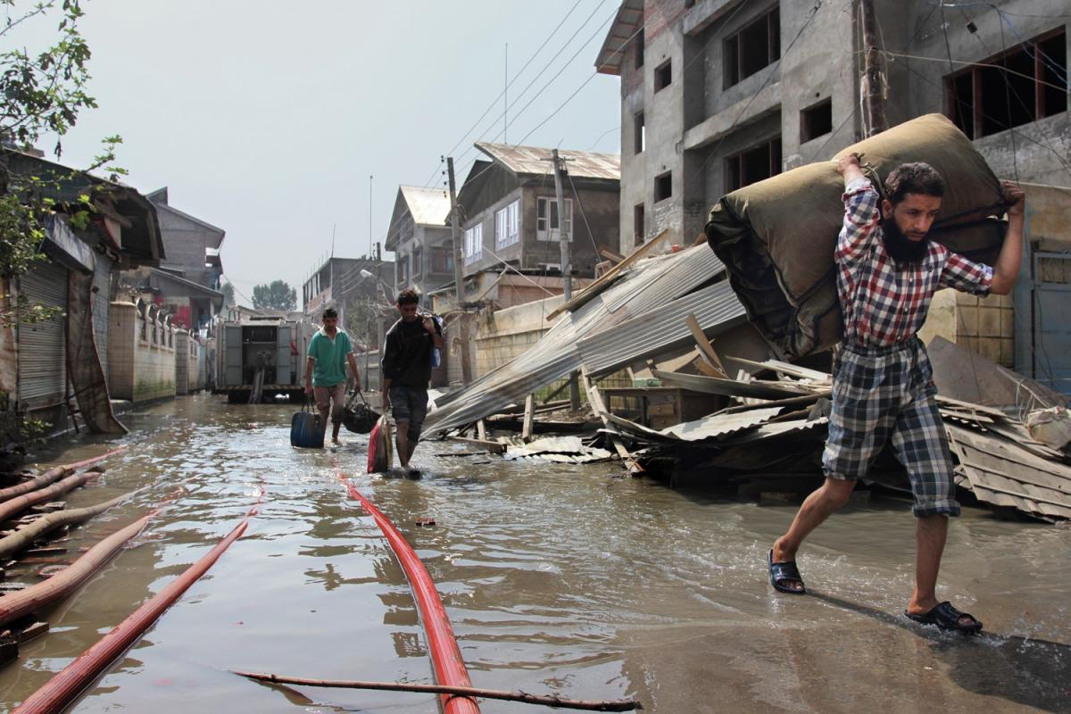 Crises, flood, man walking with supplies